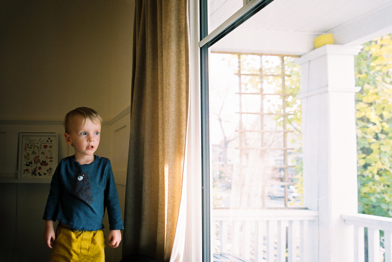 three year old boy looks out a window - Calgary in-home photography