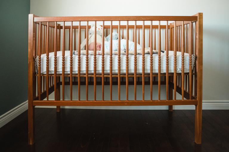 newborn baby boy sleeps in his crib