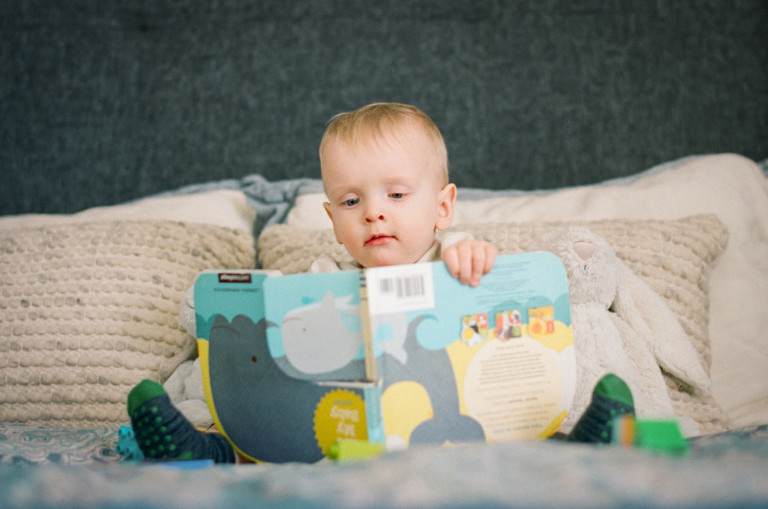 toddler reading an upside-down book