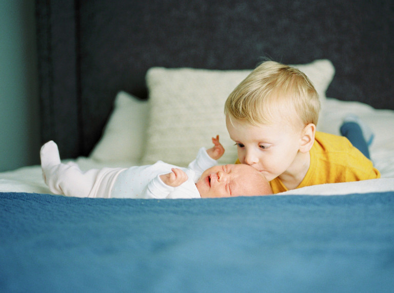 big brother kissing his newborn baby sister