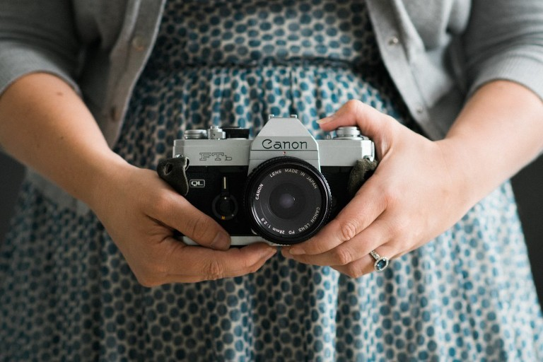 women in a blue dress holding a vintage film camera